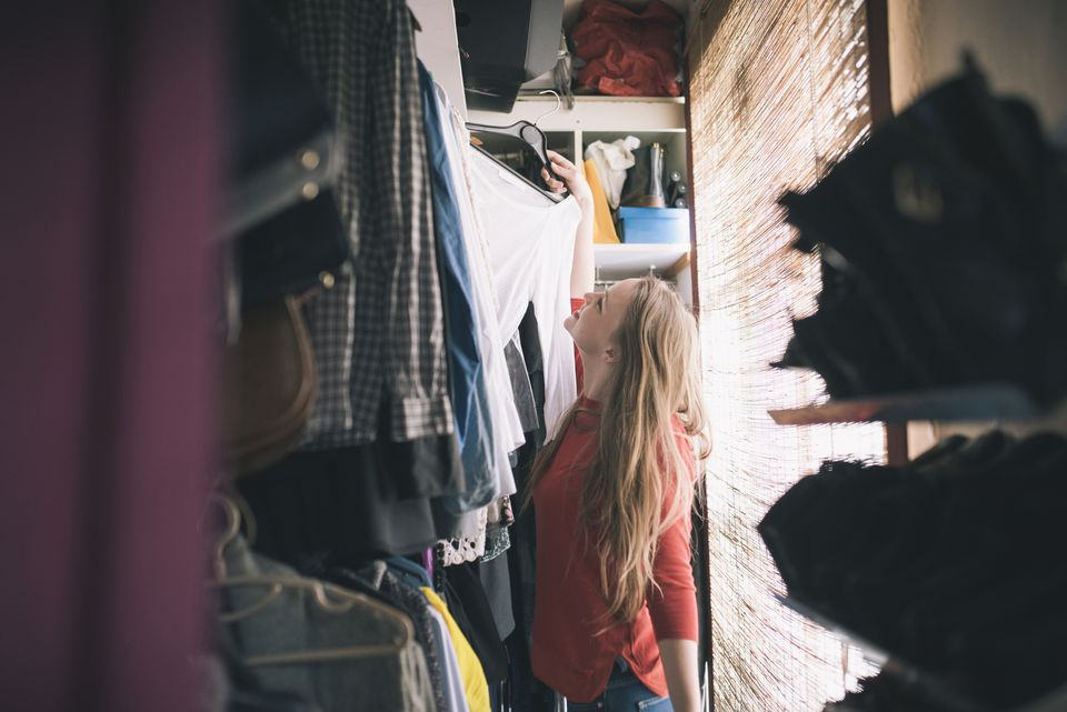 Woman gazing at clothes inside her closet.