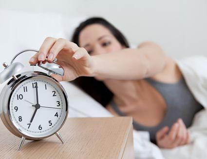 women turning off alarm clock