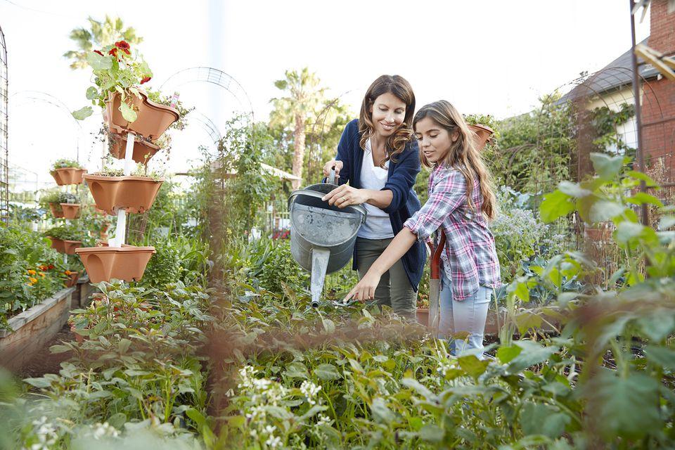 Madre e hija regando plantas en huerto