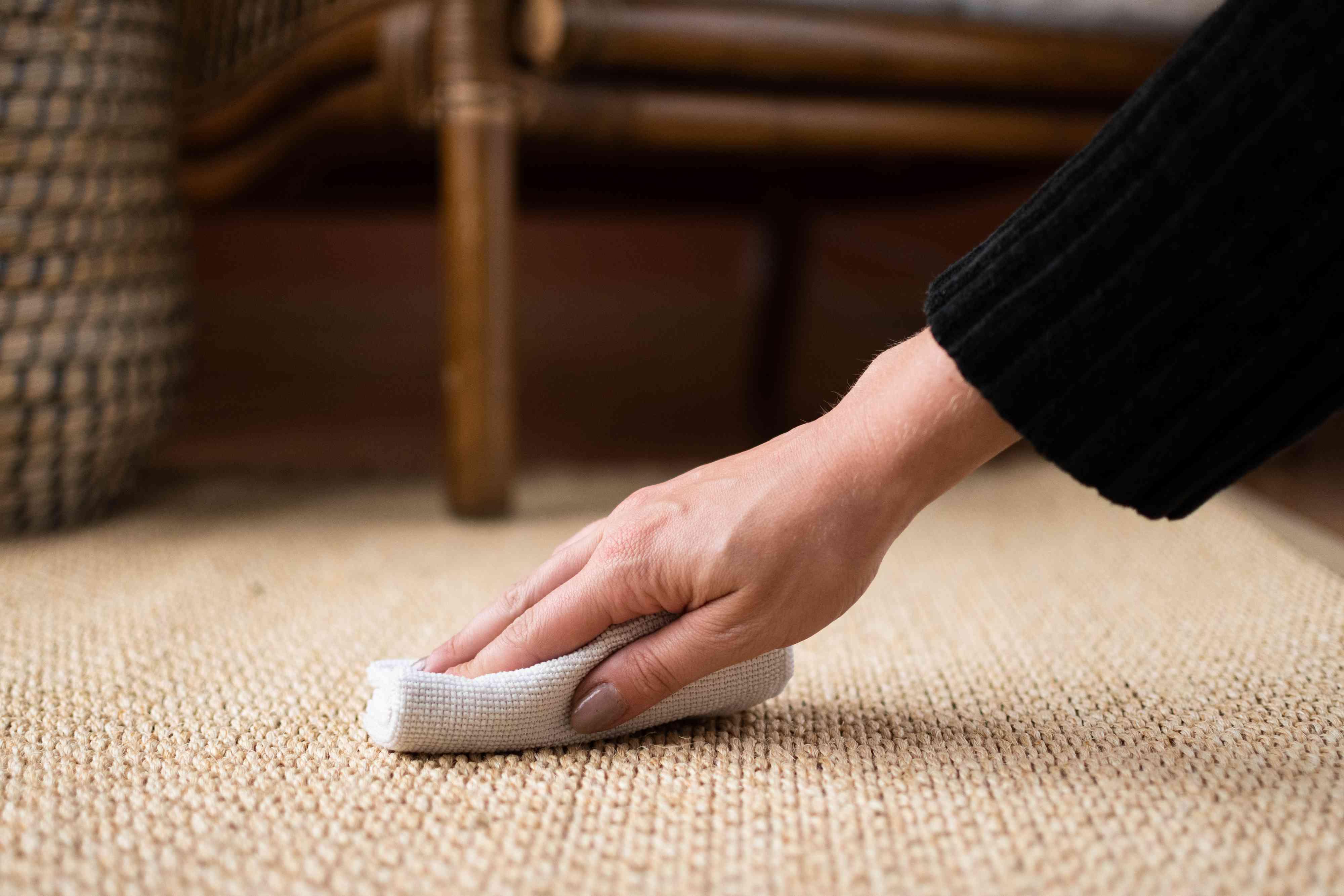 White cloth towel scrubbing and blotting sisal rug closeup