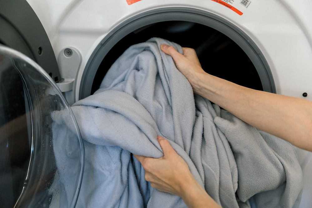 Someone removing a blanket from a washer