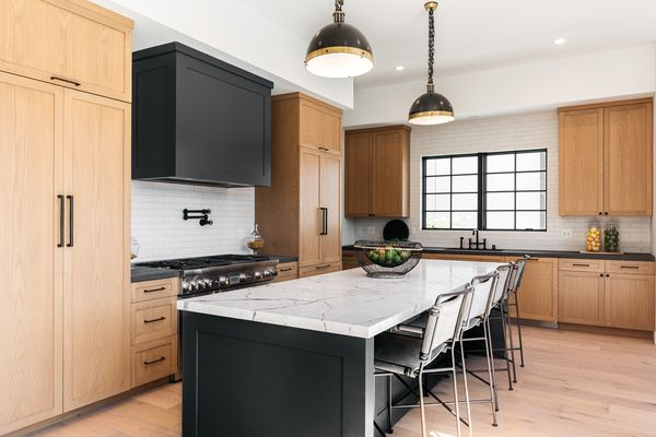 Black kitchen with wood cabinets and marble-top island in middle