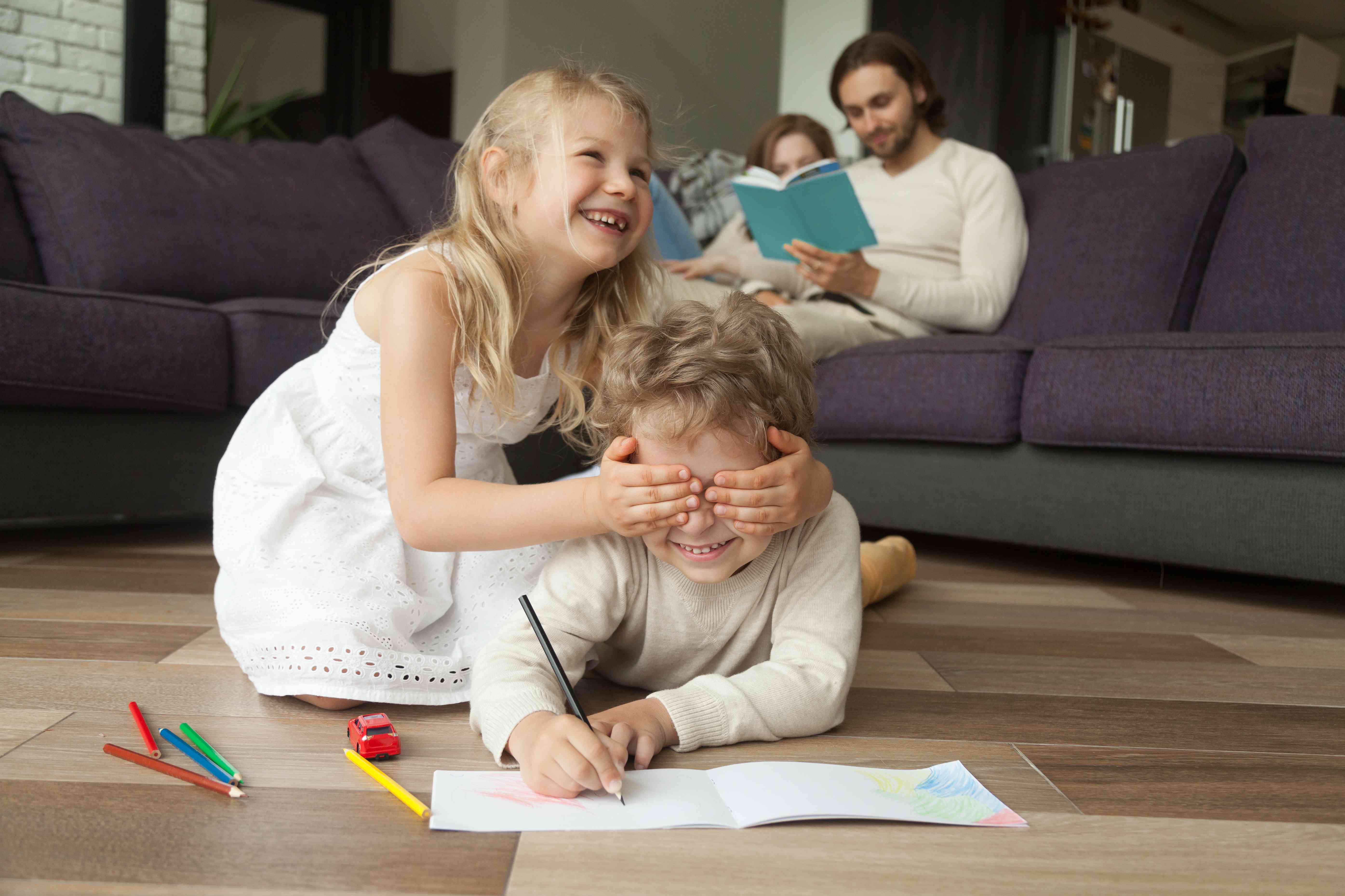 Sister closing brothers eyes with hands, family activities at home