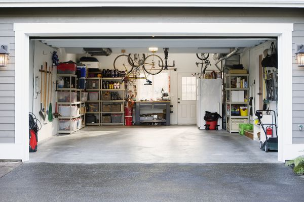 Clean car garage with shelves, tools, and bikes.