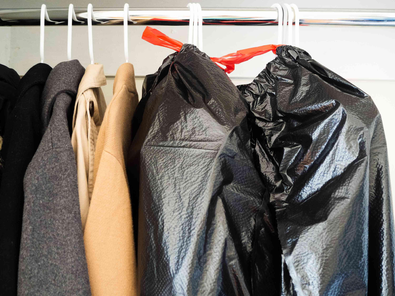 Coats hanging in closet next to black garbage bags storing wardrobe on white hangers