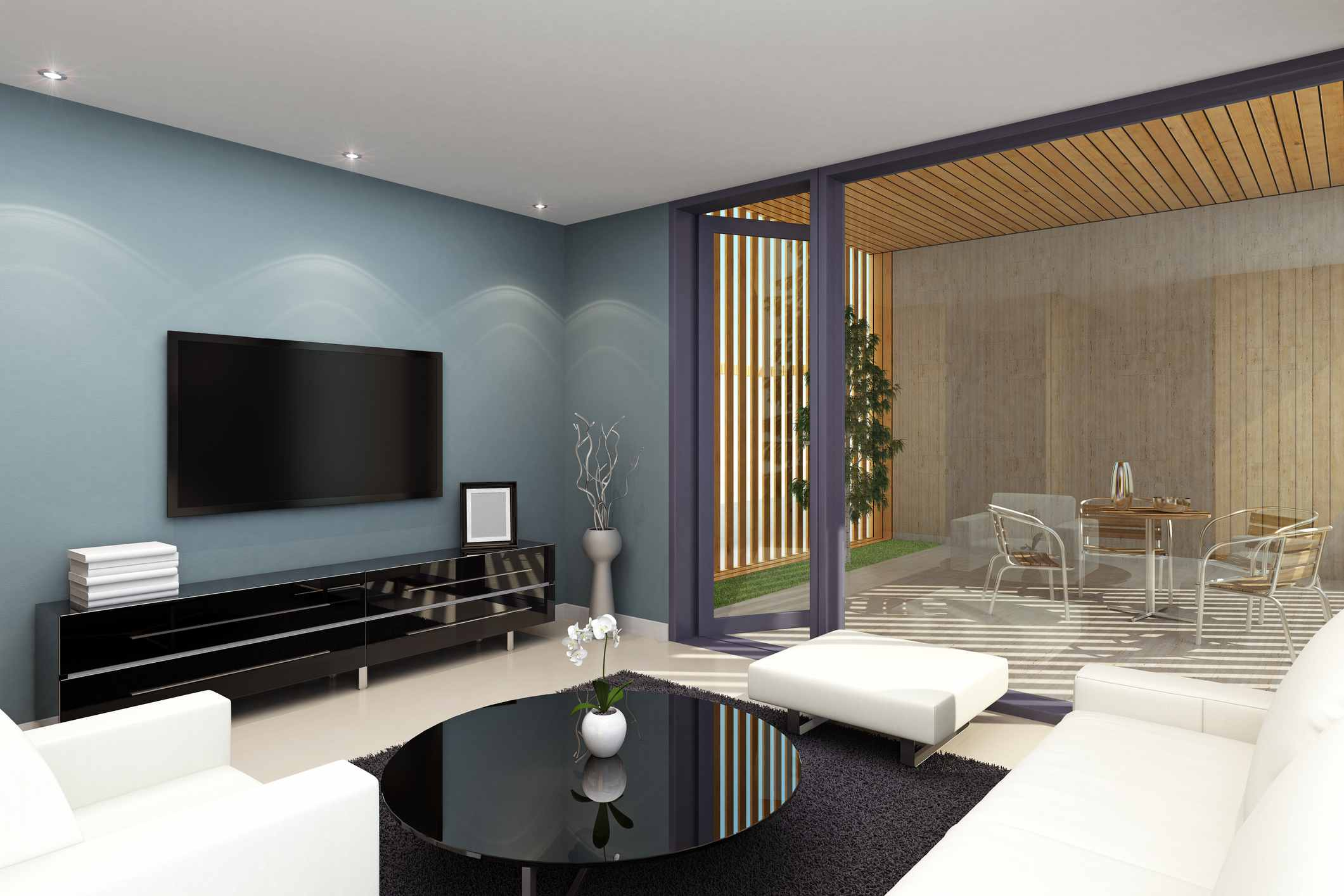 Recessed ceiling lights in a blue living room with mounted television and white chairs and couch