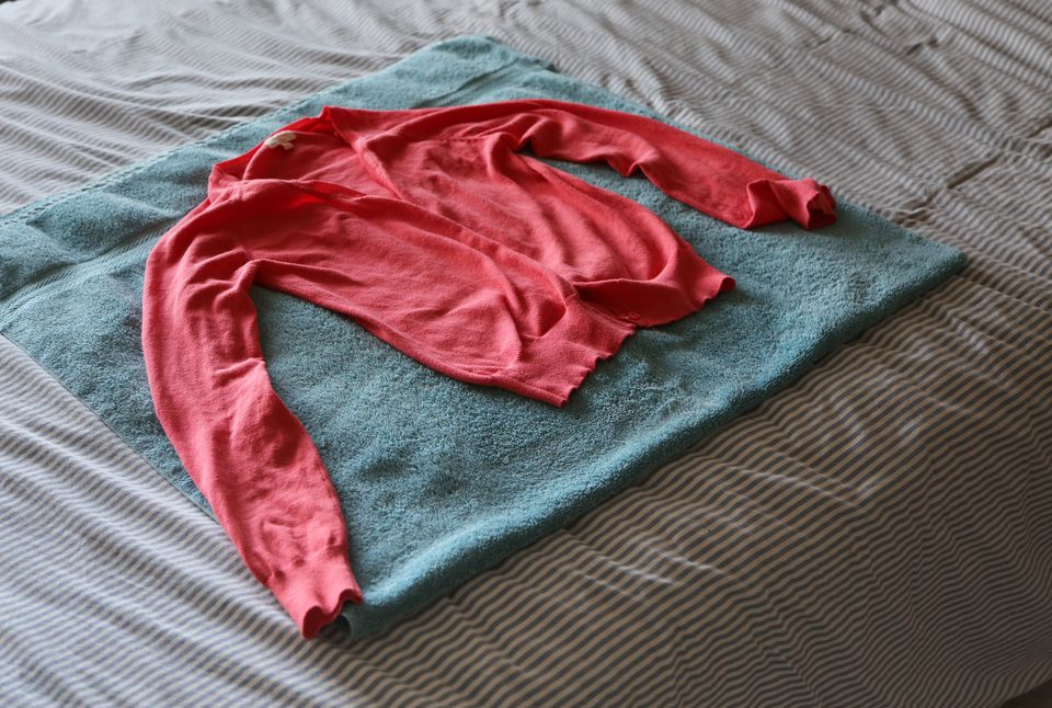 Sweater drying flat on a towel