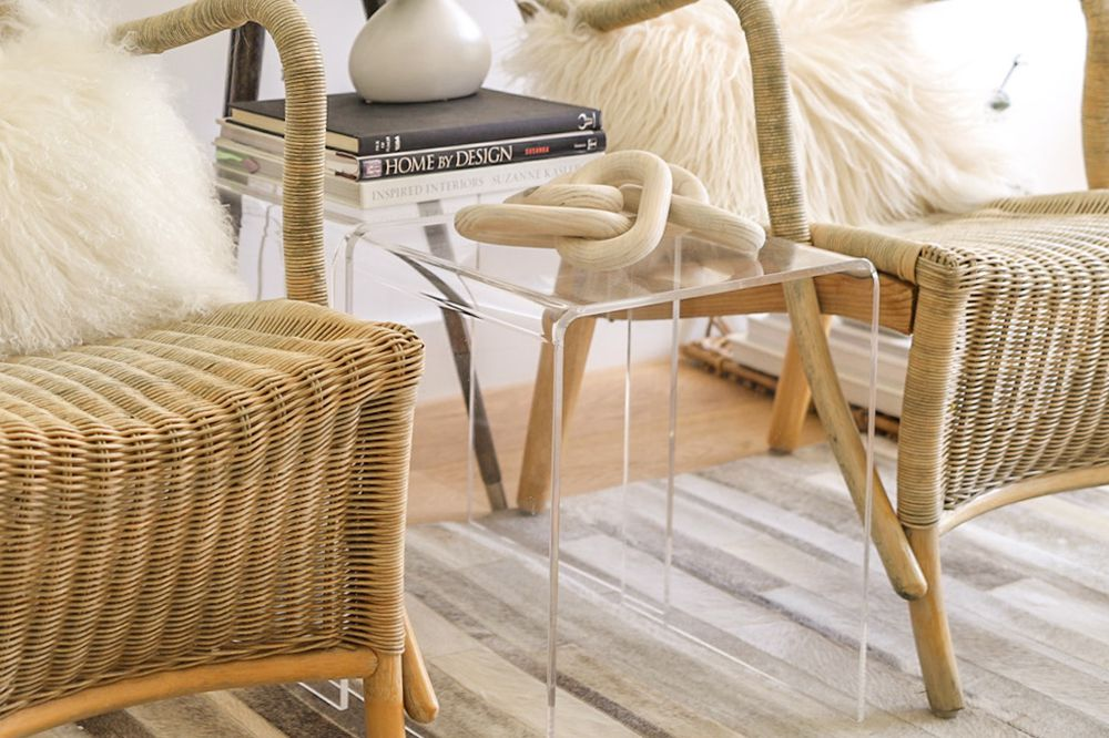 Glass side table with decorative sculpture next to stacked books and wicker chairs