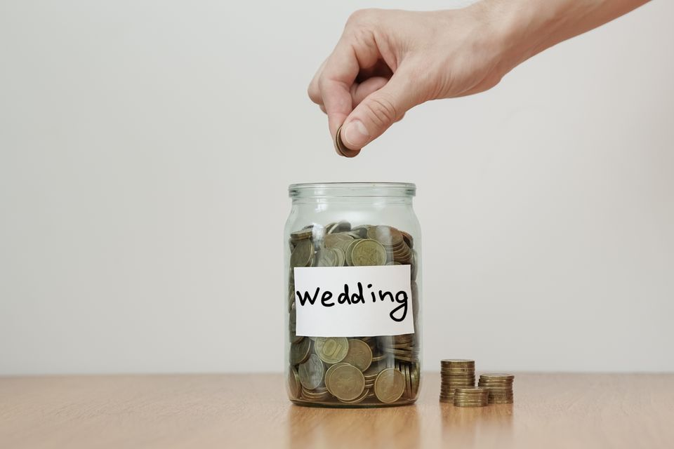 Distribution of cash savings concept. Hand puts coins to the glass money boxes with inscription 'wedding