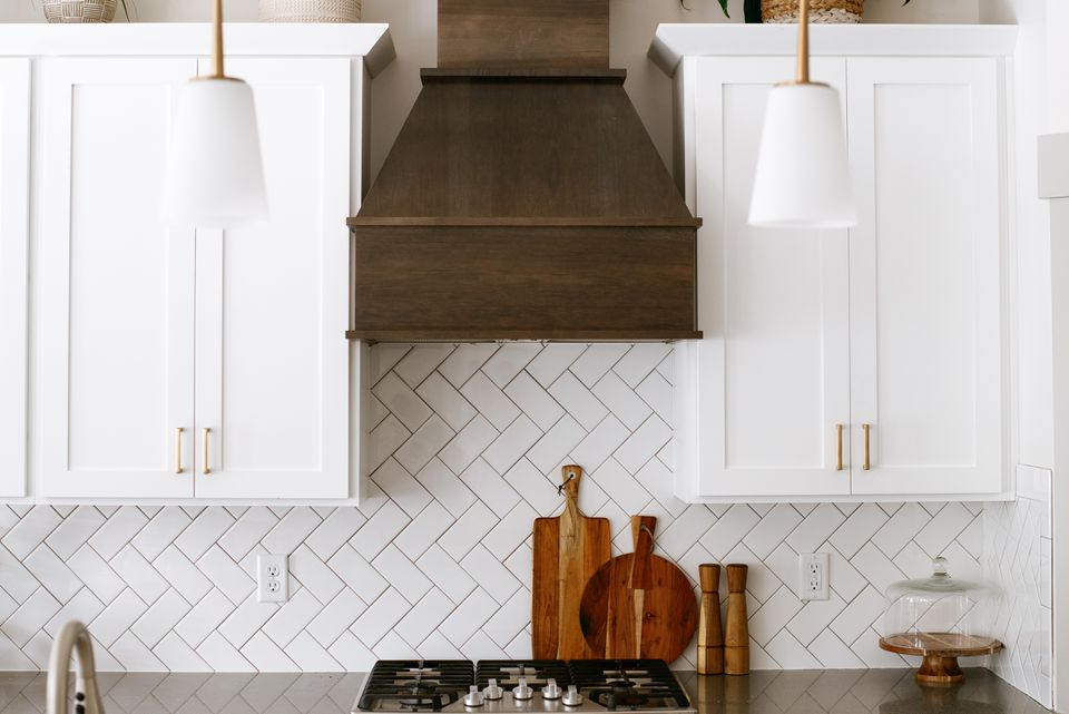 Wooden range hood next to white cabinets with a small white tiled backsplash
