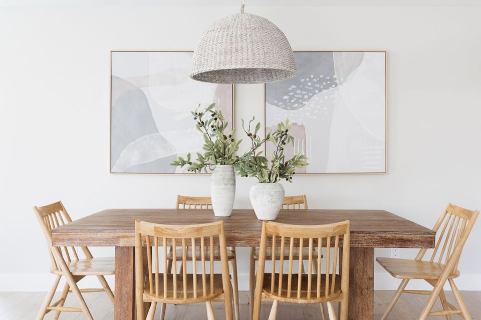 Dining room with wooden table and chairs with white vases with plants in the center in front of white walls and paintings