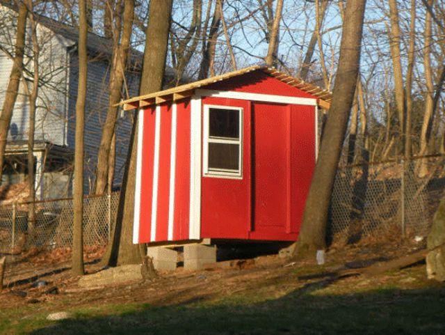 Un gallinero rojo en un patio trasero