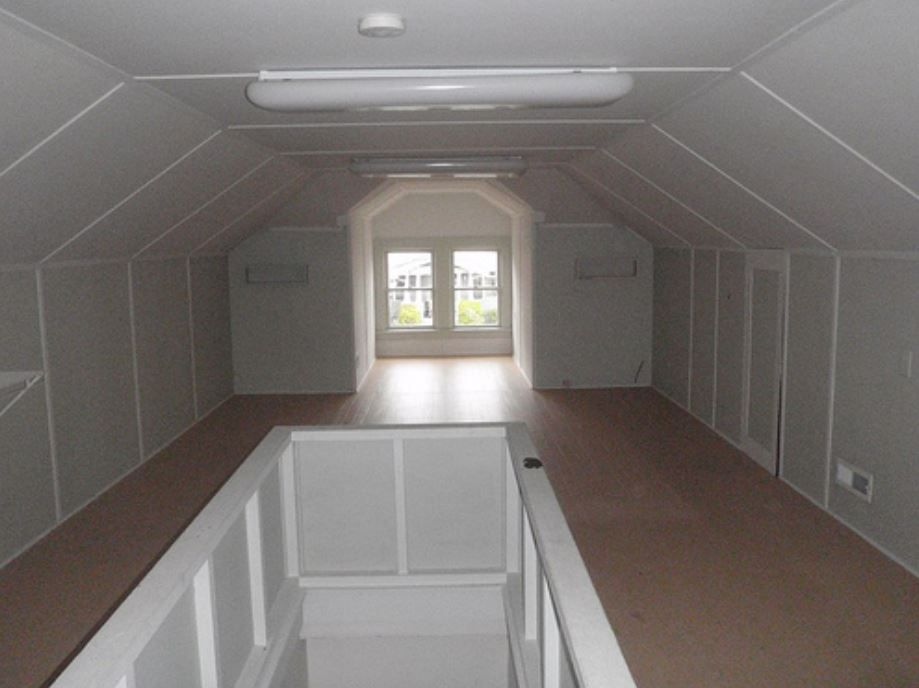 Empty finished attic space with white walls.