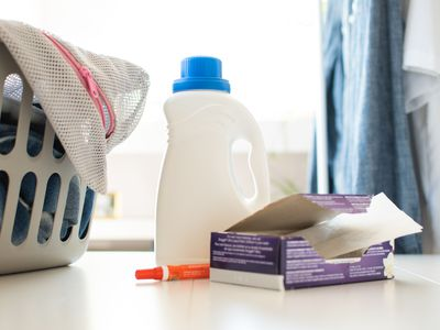 Laundry detergent and fabric softener sheets next to laundry basket