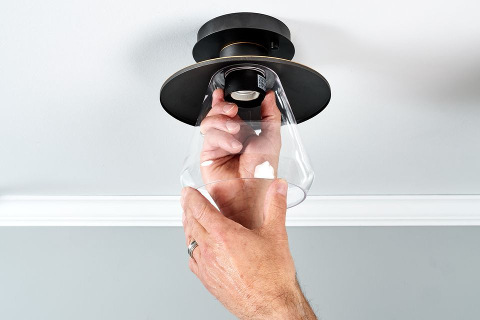 person replacing a ceiling light fixture