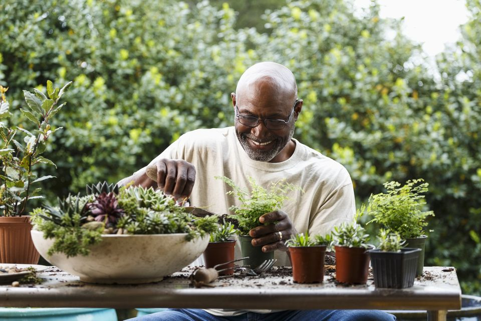 Black man gardening at table outdoors