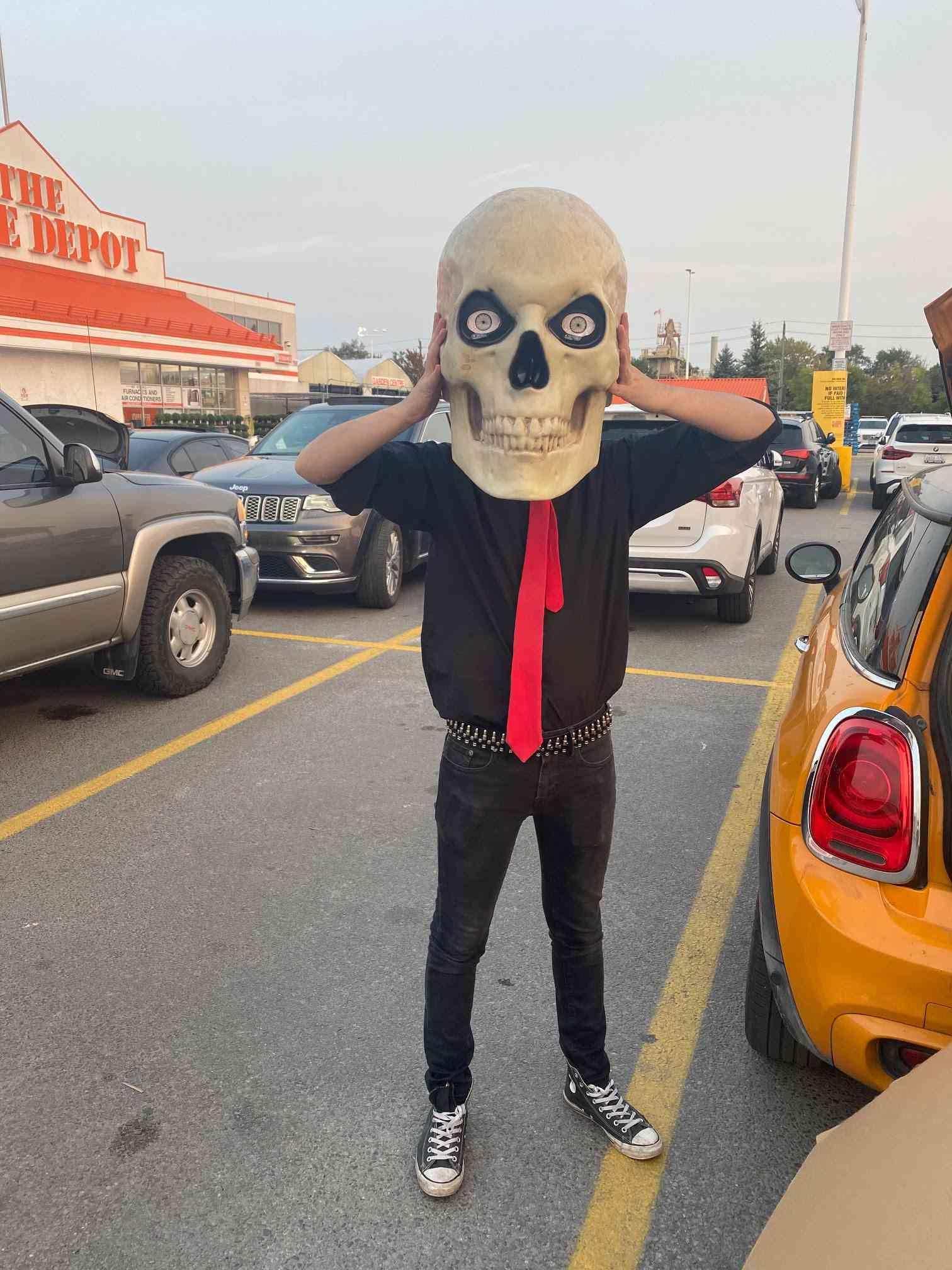 man wearing the skull of the 12-foot-skeleton