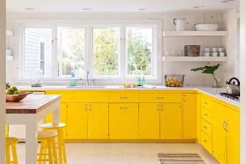 Modern farmhouse kitchen with yellow cabinets and yellow stools.