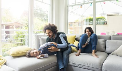 Happy family sitting on couch, father tickling his laughing daughter
