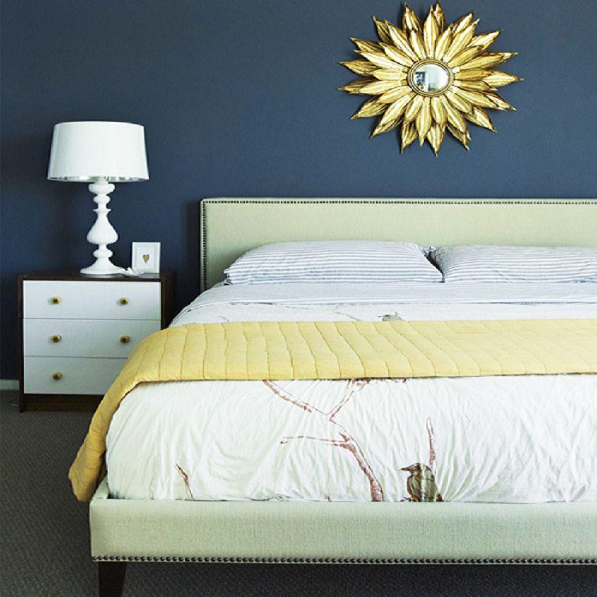 Bedroom with dark blue walls and sunburst mirror