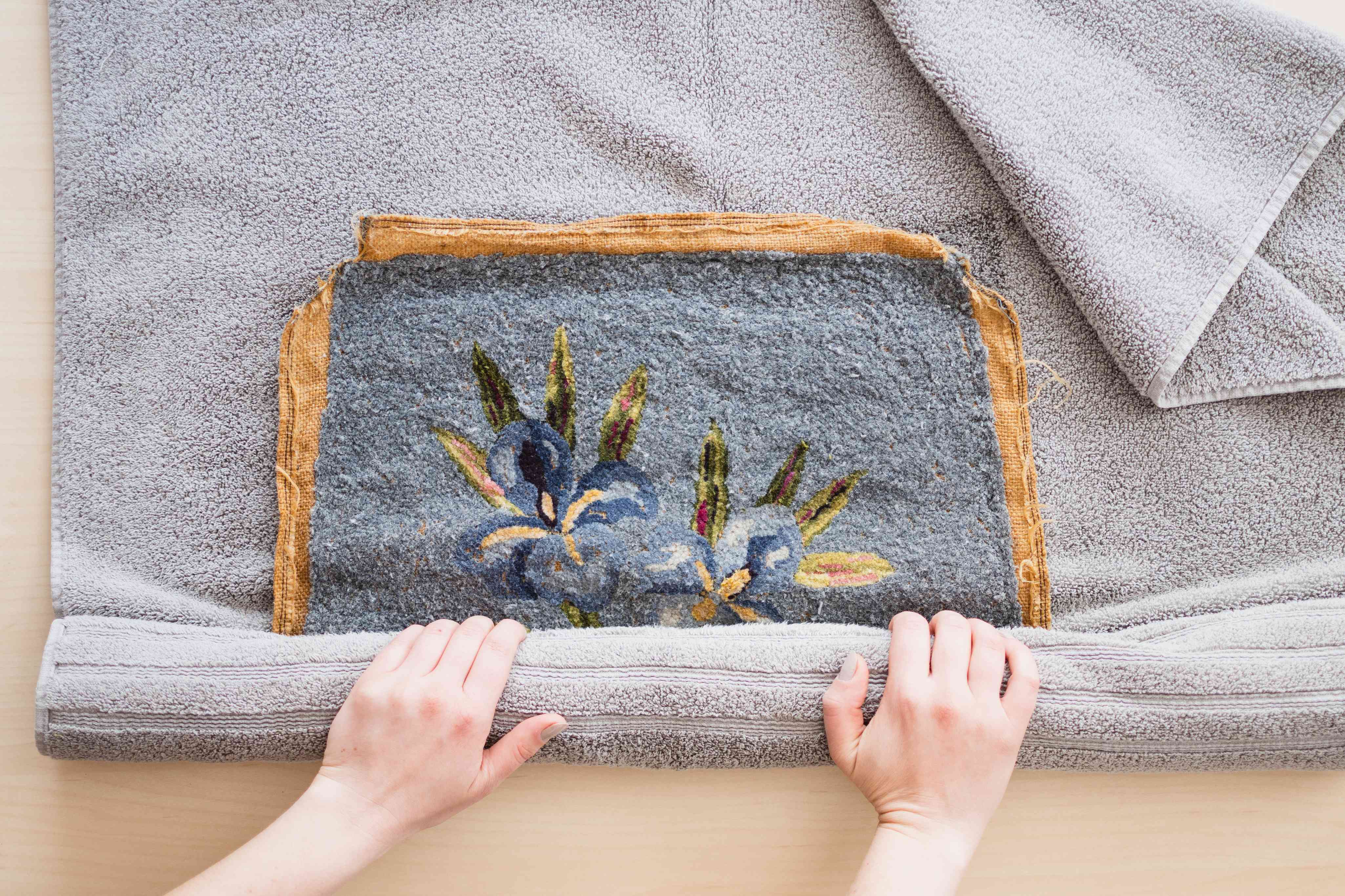 Needle point art piece rolled into gray towel to dry