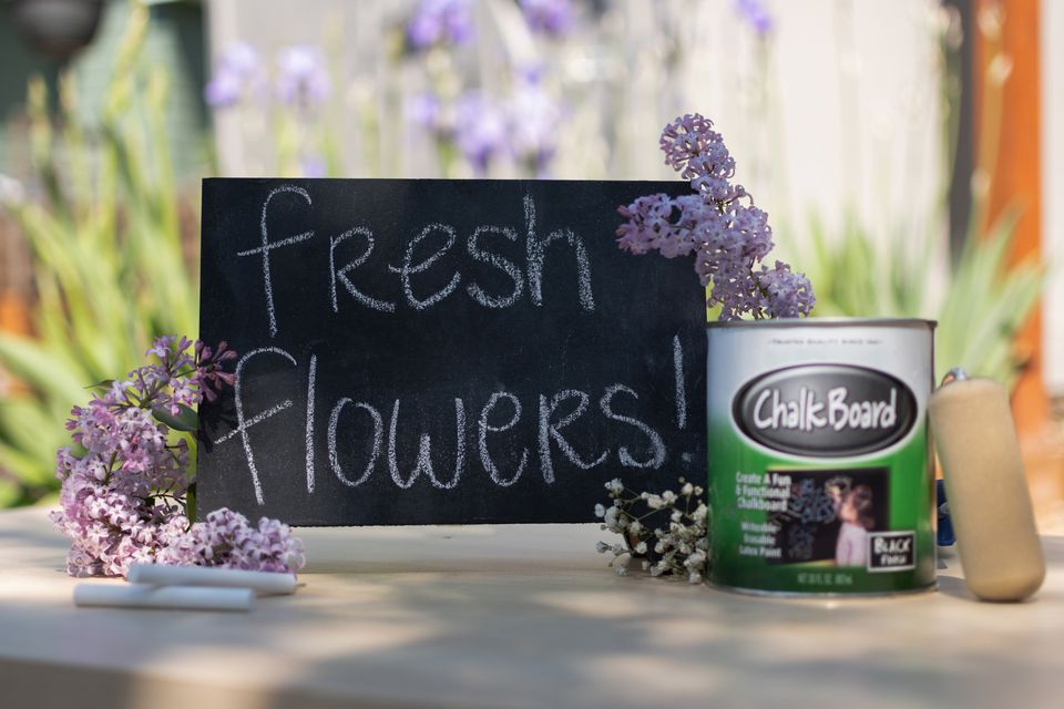 Sign made with chalkboard paint bucket in front of fresh flowers and paint roller