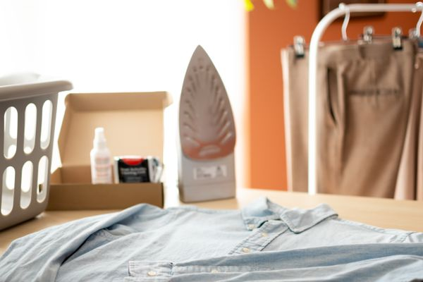 Light blue button down shirt in front of iron, white basket and dry cleaning materials