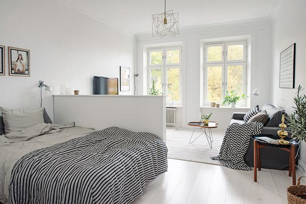 A low, temporary wall sits in a bright and airy room, separating a bedroom from a living area.