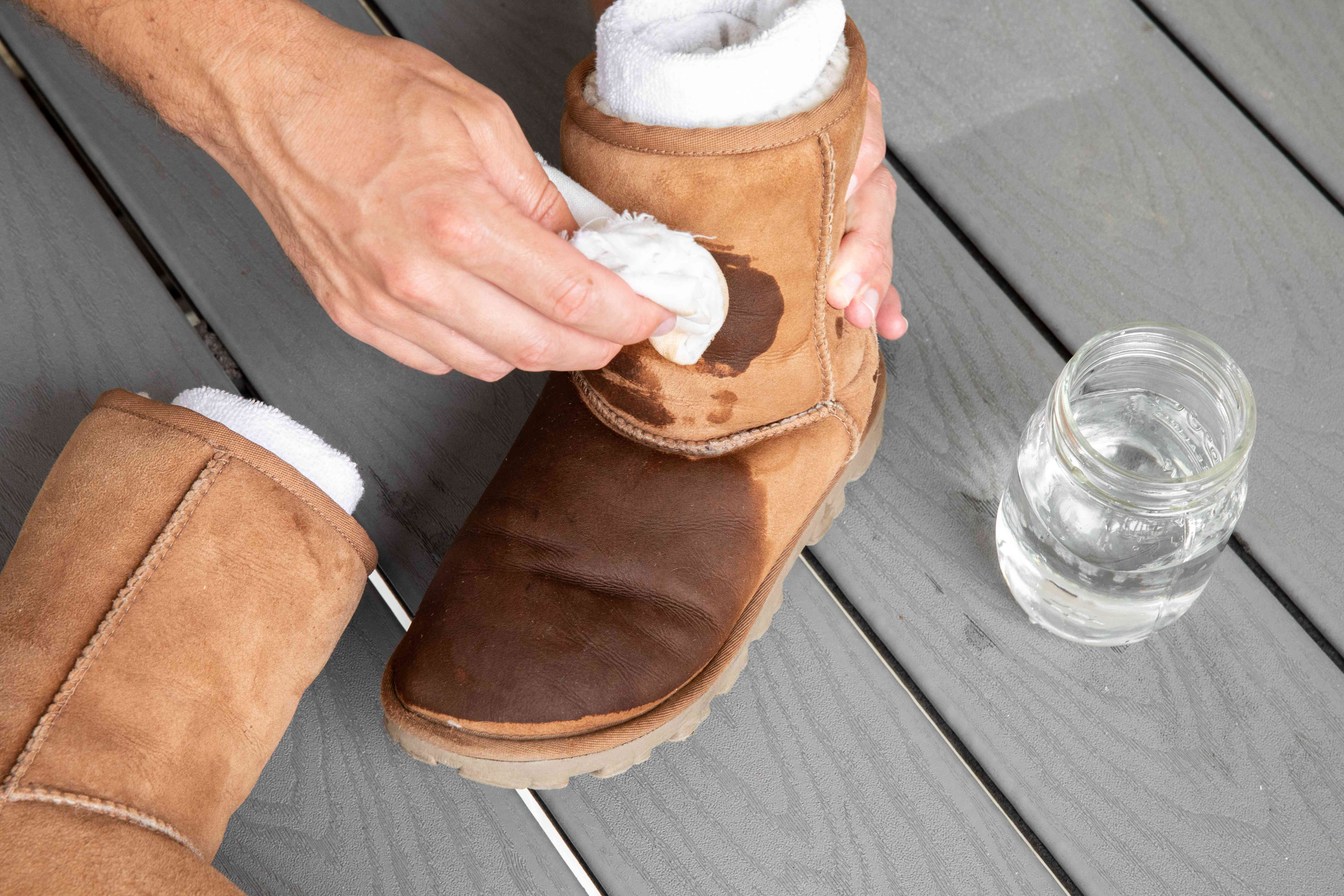 Someone dabbing Ugg boots with a vinegar solution