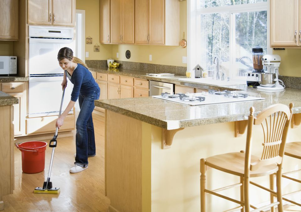 Teenage girl (16-18) mopping kitchen floor