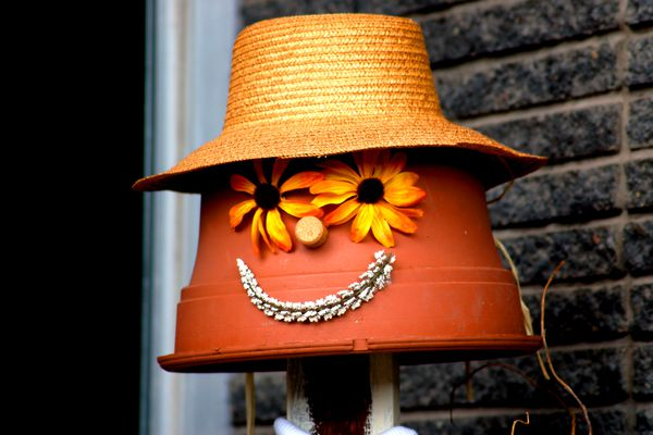 scarecrow with an upside-down pot for a head and a straw hat