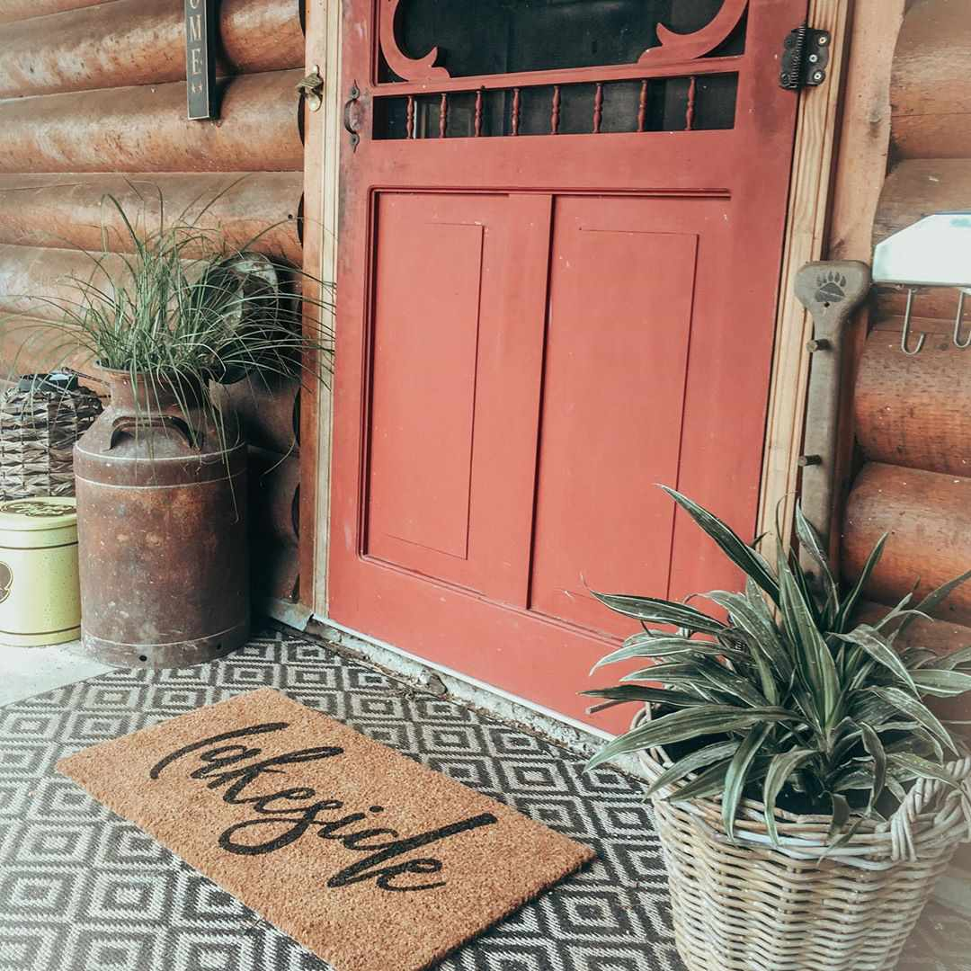 Entryway with a red door and welcome mat