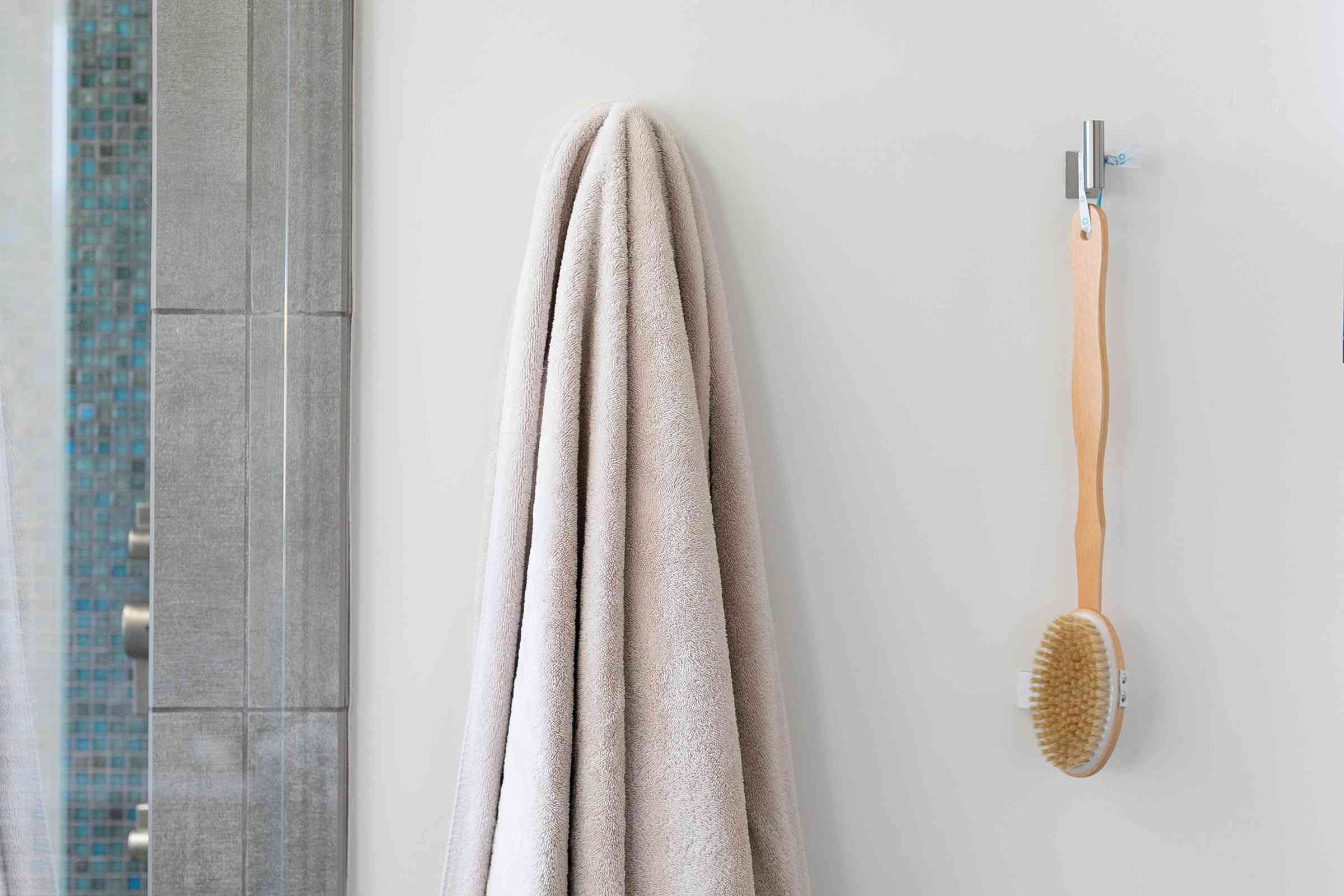 Bathroom hooks with towel and body brush hanging in guest bathroom