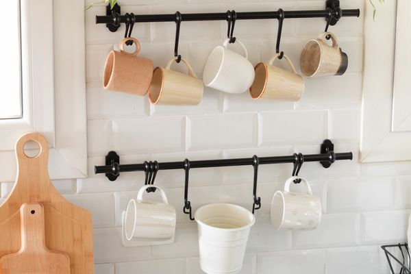 mugs hanging from hooks on the wall