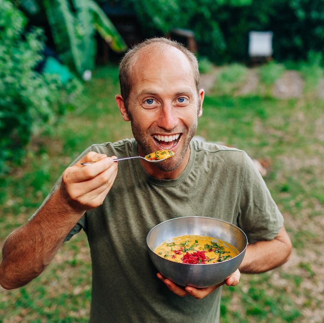 A man eating out of a bowl looking at the camera