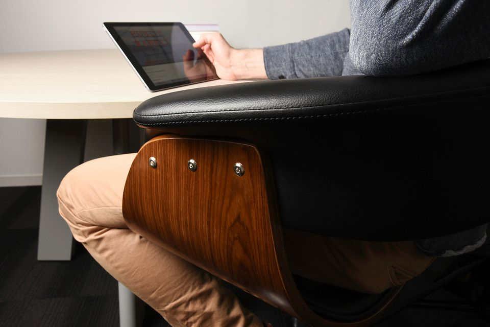 A man looking at a tablet while sitting in an office chair