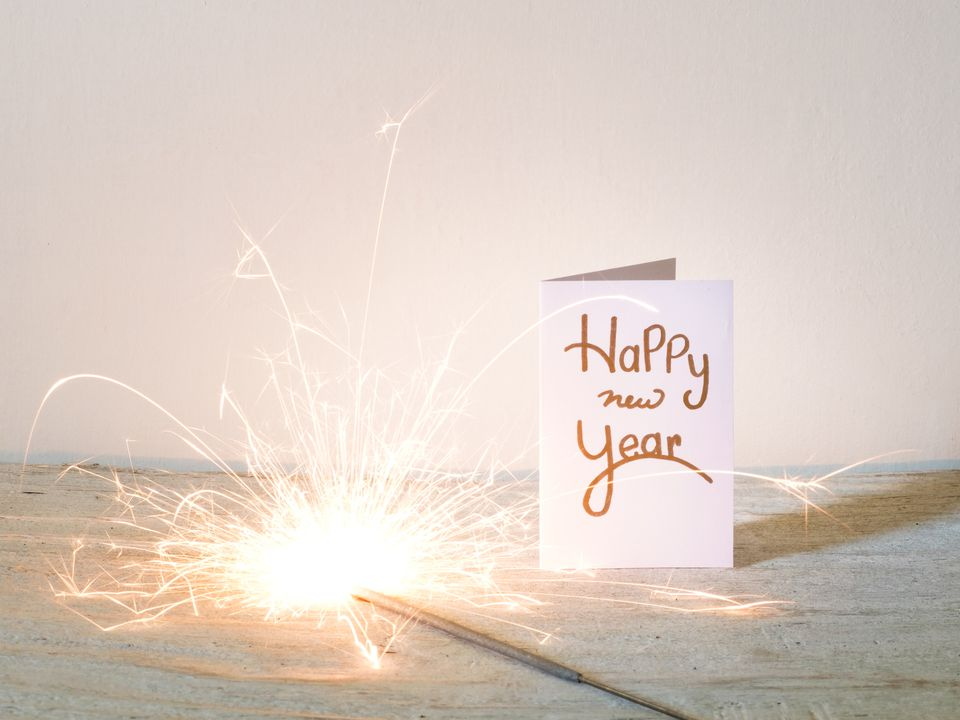 Happy New Year card next to a lit sparkler