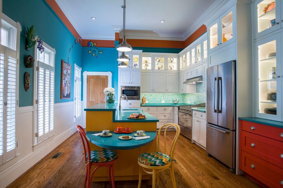 Cocina comedor tropical con paredes azules brillantes y una pequeña mesa azul con sillas rojas y amarillas