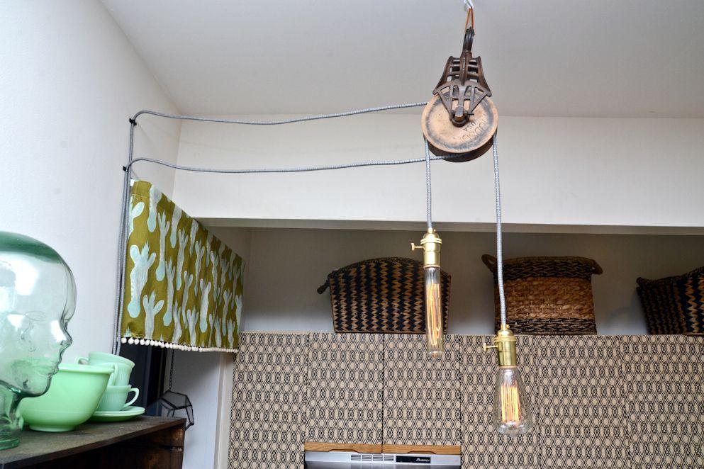 Poleas de granero reutilizadas como luces colgantes con bombillas de filamento expuestas