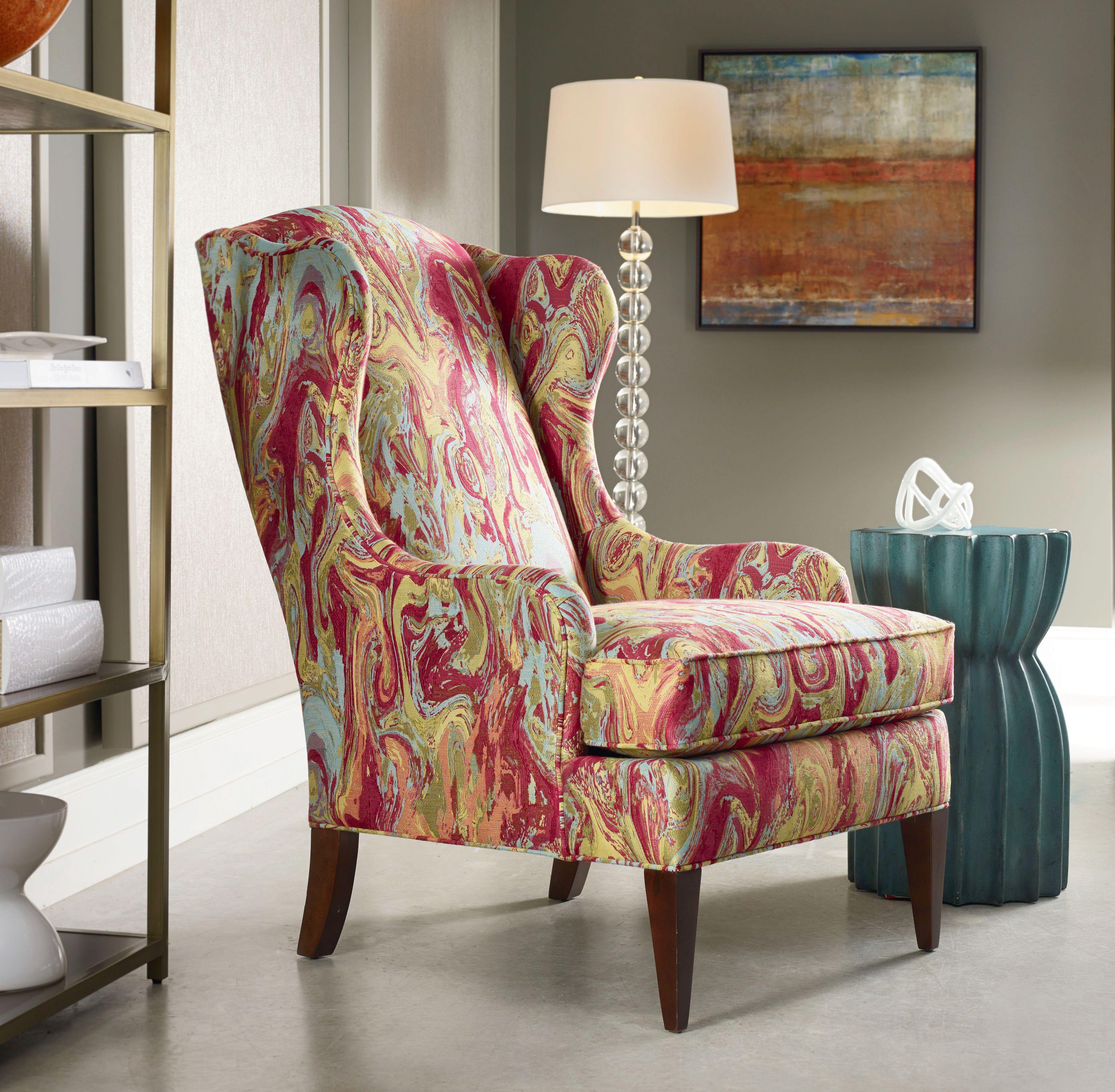 Silla colorida Euphoria de Sam Moore en una sala de estar cerca de una lámpara de pie. , Una silla estampada de Newport con una almohada marrón