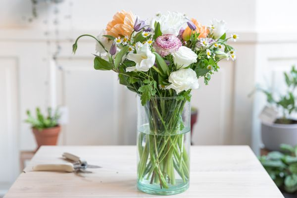 Floral arrangement with various flowers in a glass vase with water