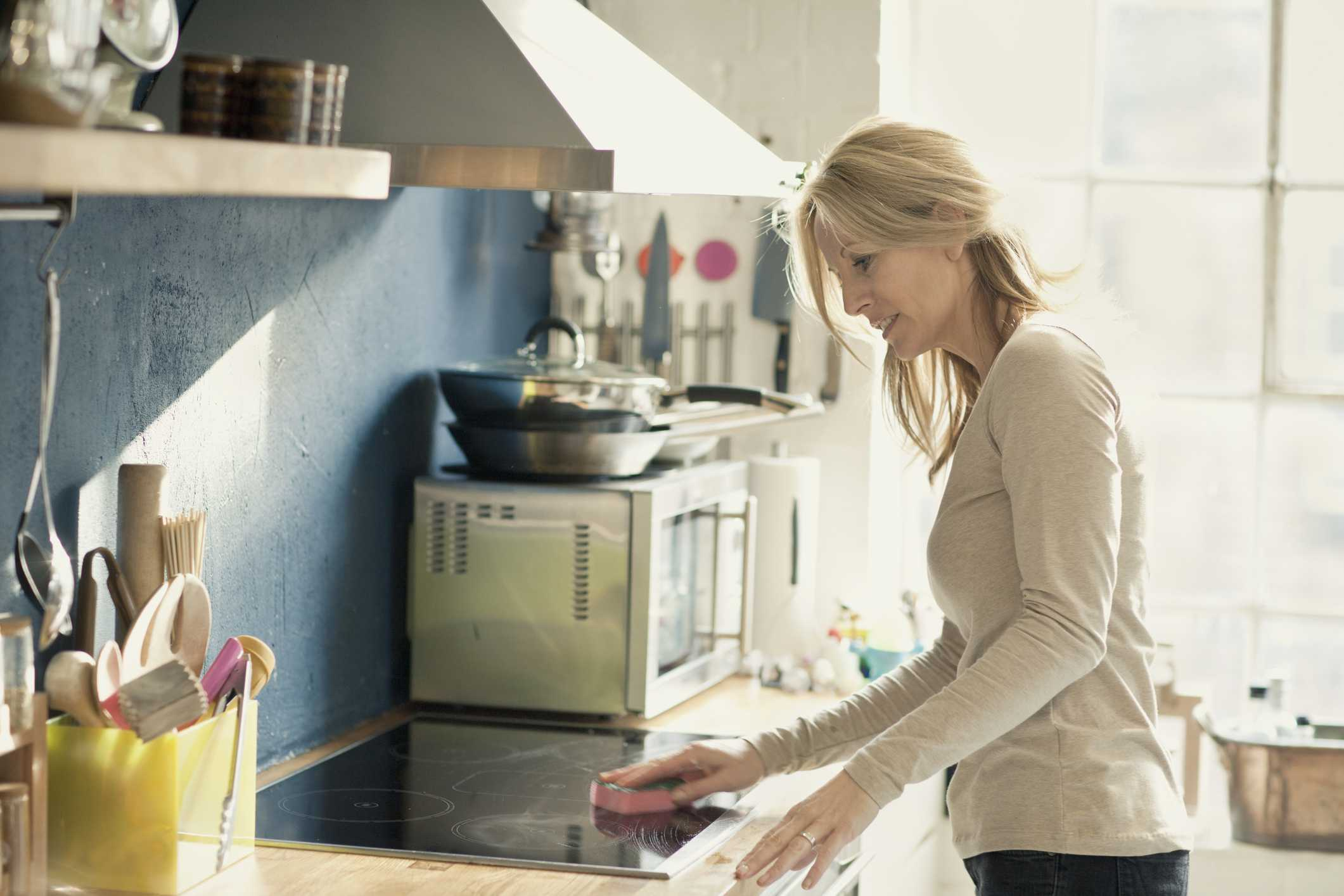 Mujer limpiando su electricidad estufa en su cocina
