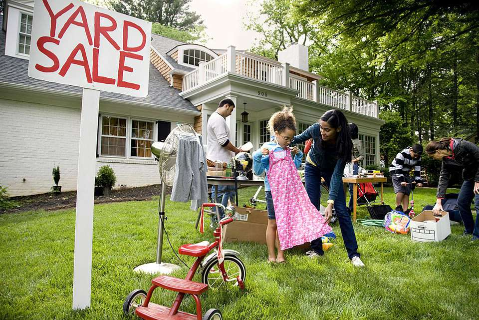mother buying children's clothes at yard sale