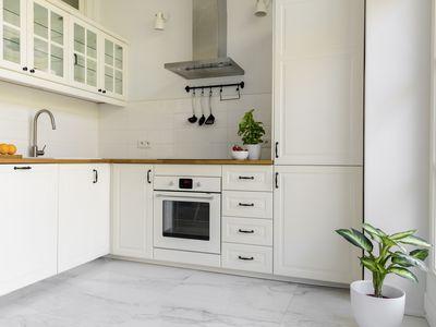White kitchen interior with marble flooring