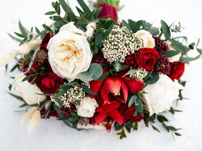 Wedding bouquet of red and white roses flowers on the white snow