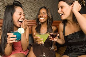 Three women holding drinks and laughing
