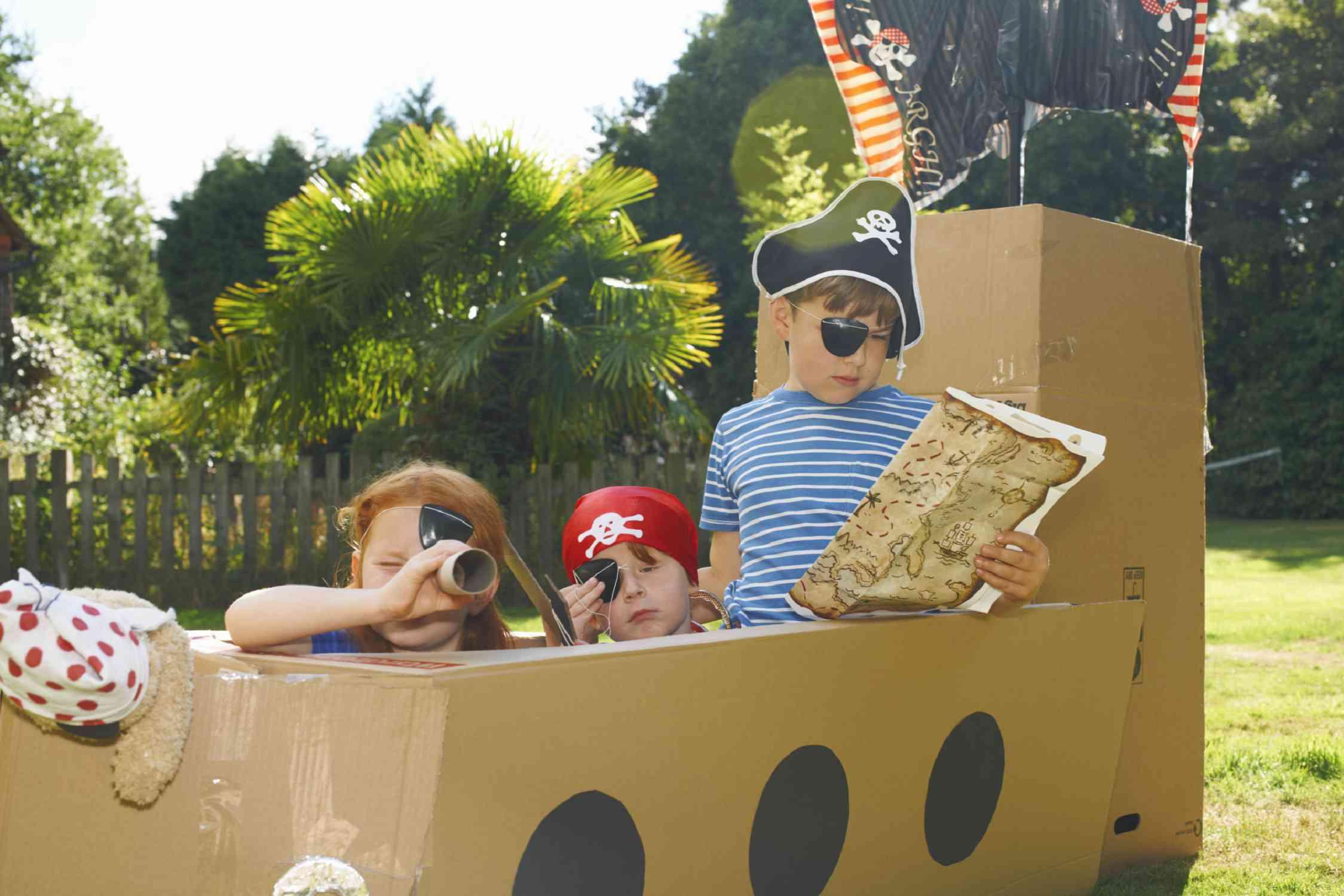 kids playing on a cardboard pirate ship