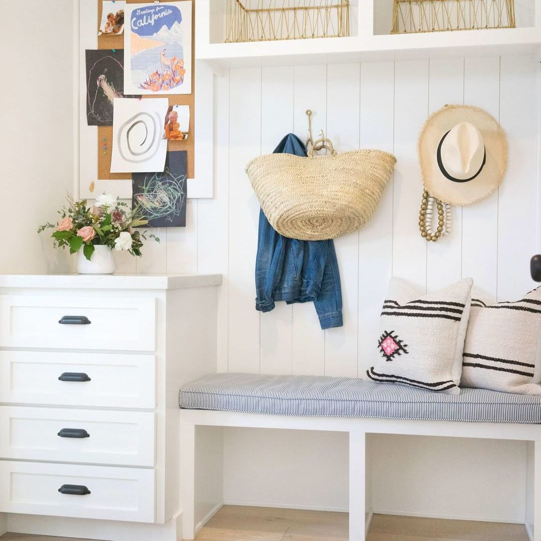 A mudroom with white drawer storage, a hanging bag and straw hat and memo board.