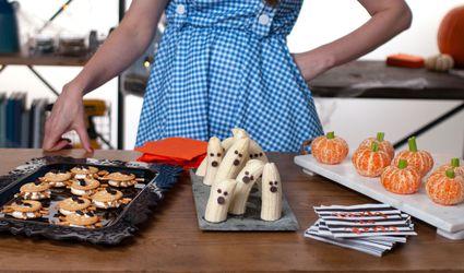 Woman standing behind table of Halloween snacks