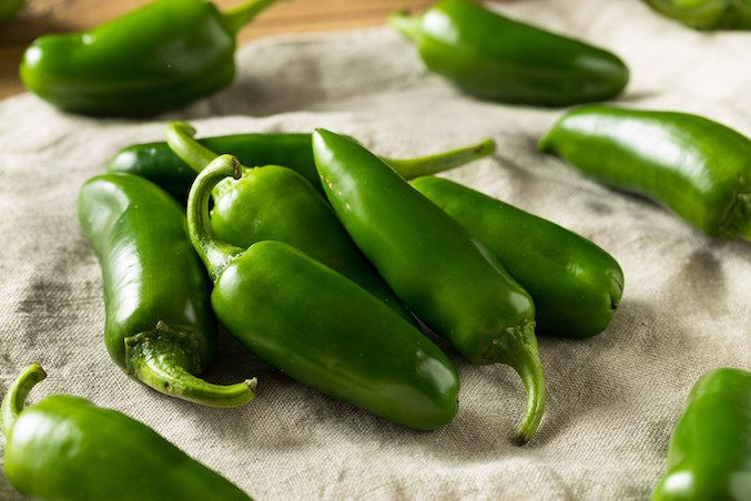 Bright green Serrano peppers on a beige linen cloth